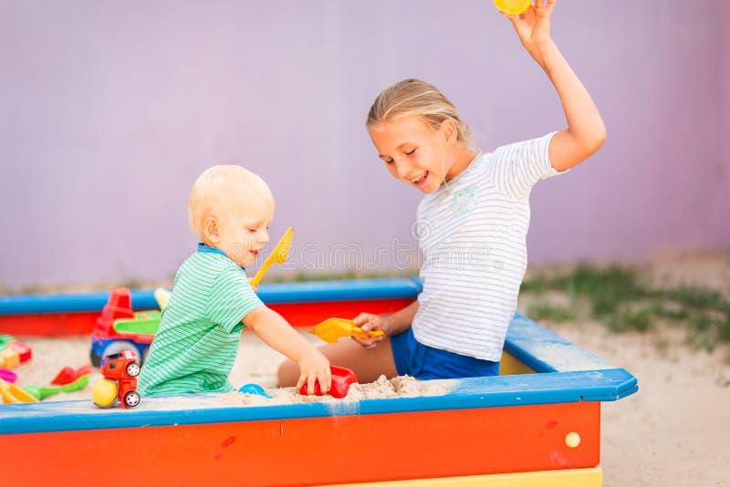 Nettes Baby, das mit seiner Schwester im Sandkasten spielt stockbilder
