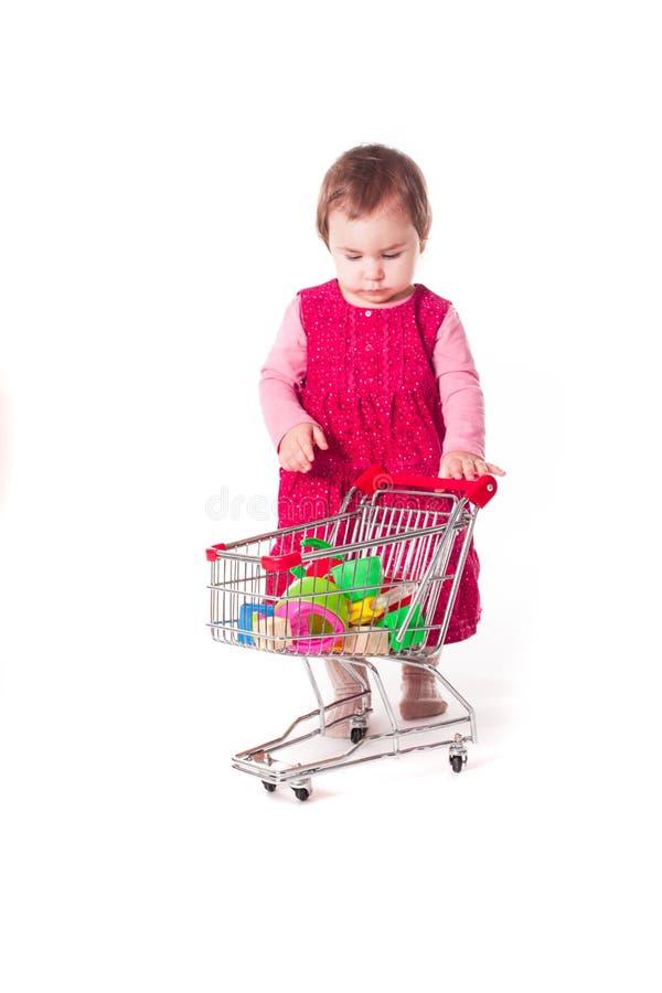 Nettes Baby, das mit Spielzeugwarenkorb spielt stockfoto