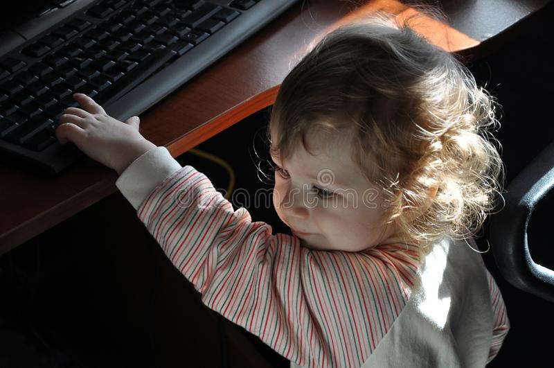 Nettes Baby, das mit Tastatur spielt stockbild