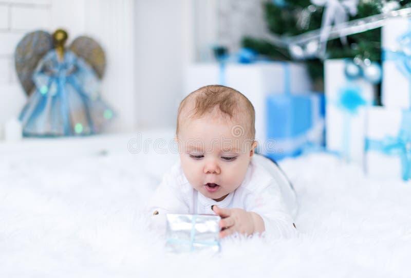 Nettes Baby, das mit Weihnachtsgeschenk im Reinraum spielt stockfoto