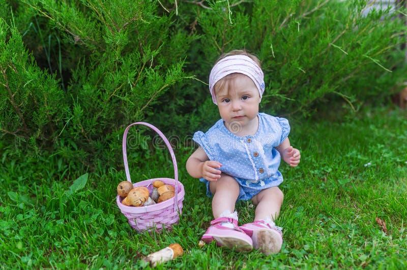 Nettes Baby, das Pilze in einem Herbstwald erfasst und im Gras sitzt lizenzfreies stockfoto