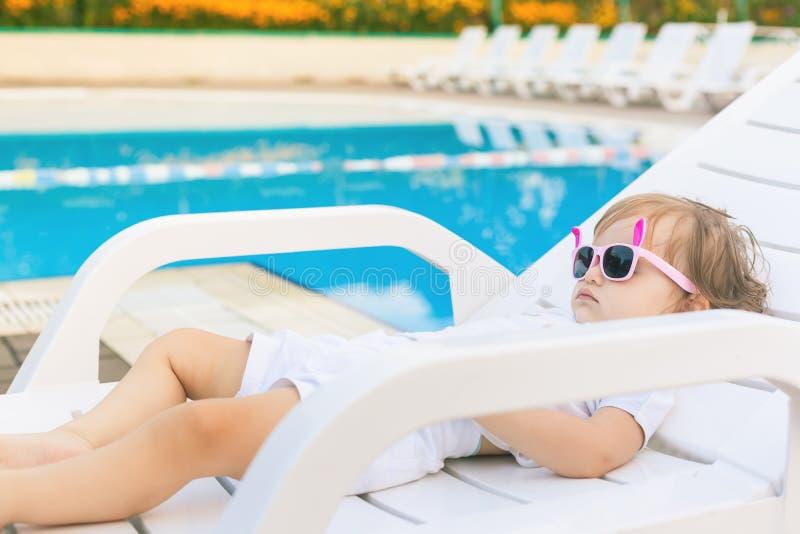 Nettes Baby, das an sunbed nahe Pool in Hawaii, Hotel sich entspannt stockfotografie