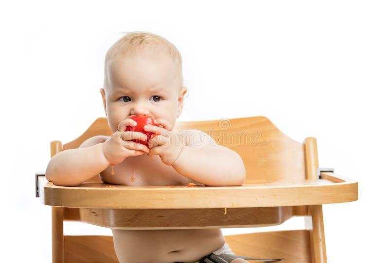 Nettes Baby, das Tomate beim Sitzen im Hochstuhl isst stockfotos
