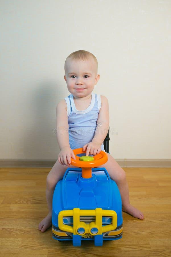 Nettes Baby, das zu Hause ein Spielzeugauto fährt lizenzfreie stockbilder