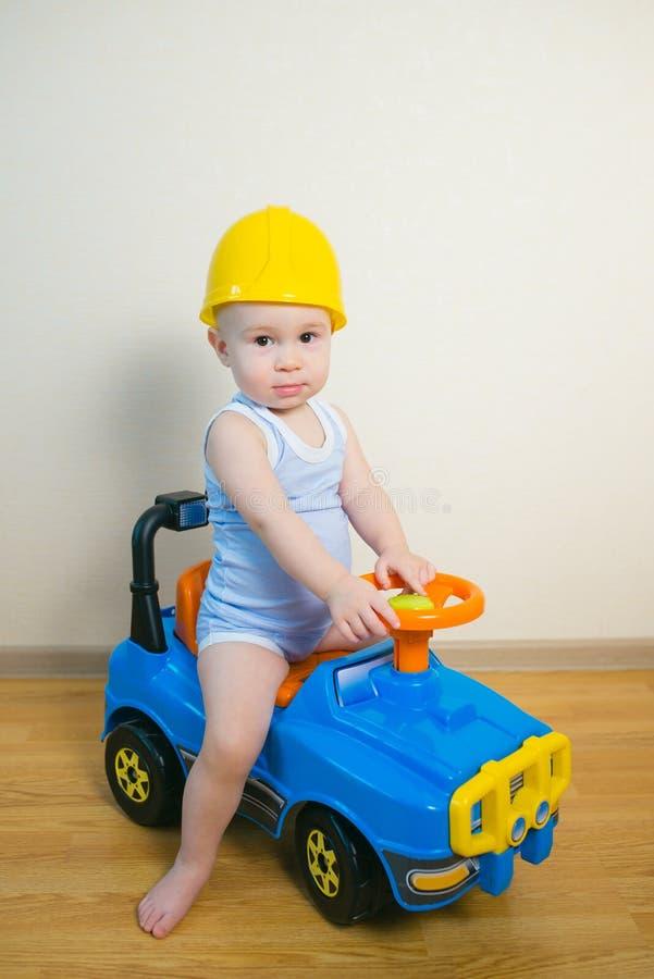 Nettes Baby, das zu Hause ein Spielzeugauto fährt lizenzfreies stockbild