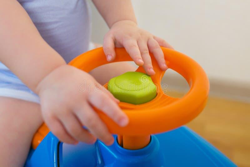 Nettes Baby, das zu Hause ein Spielzeugauto, Nahaufnahmehände auf Steuer fährt lizenzfreies stockbild