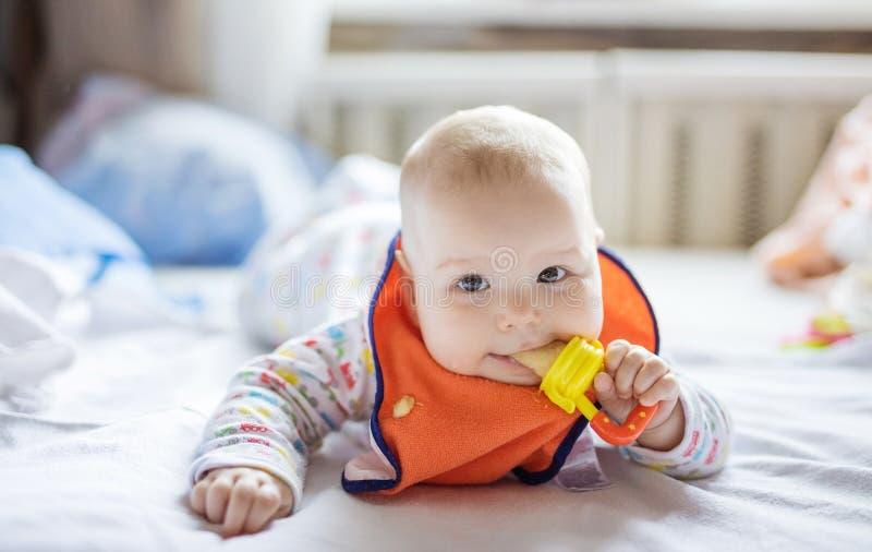 Nettes Baby, das zu Hause Frucht im Nibbler auf Bett isst stockfotos