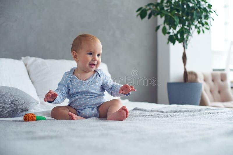 Nettes Baby, das zu Hause mit gestricktem Spielzeug auf Bett spielt lizenzfreie stockfotos