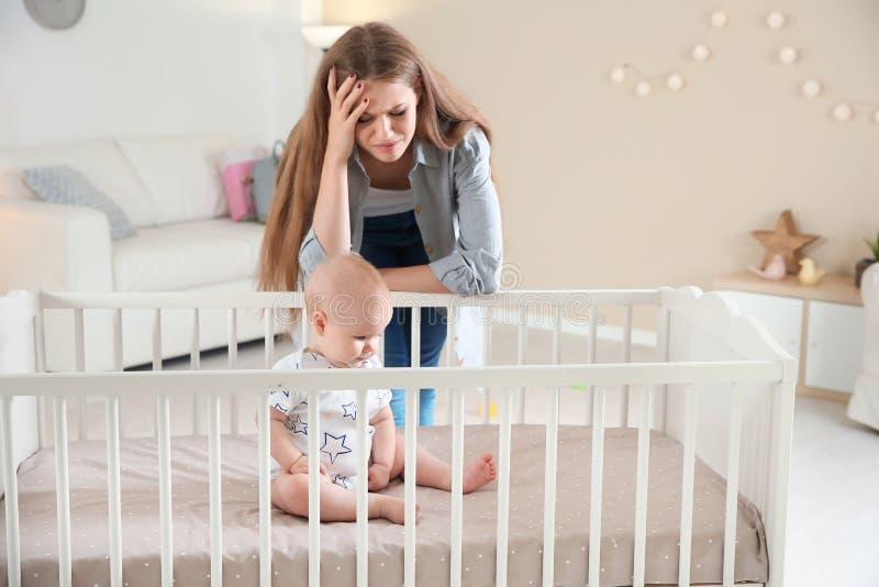 Nettes Baby in der Krippe und in der jungen Mutter lizenzfreie stockbilder