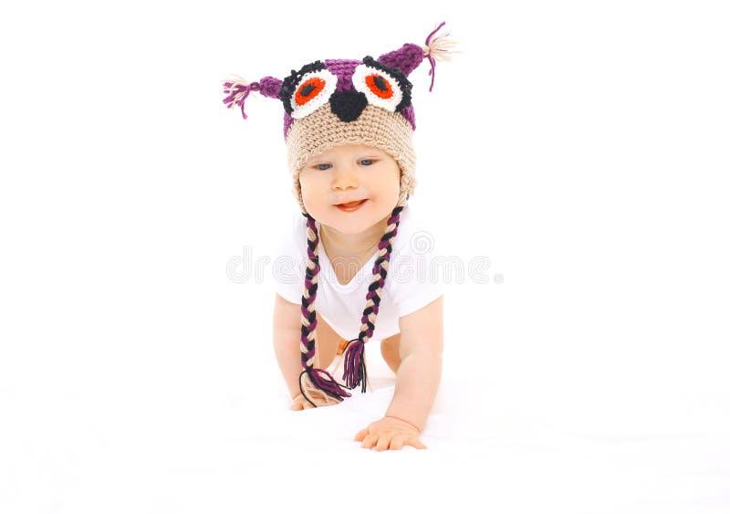 Nettes Baby in der Strickmütze kriecht auf Weiß lizenzfreie stockfotografie