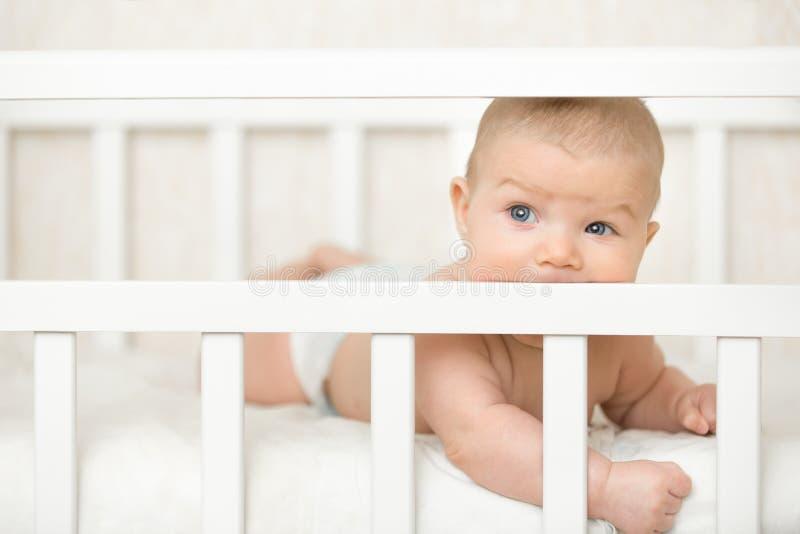 Nettes Baby in einem Feldbett, welches das hölzerne Brett saugt stockfotos