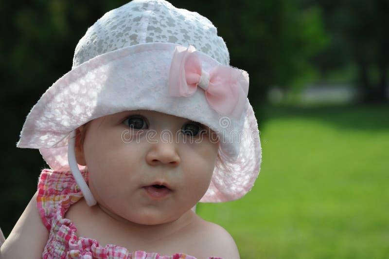 Nettes Baby in einem Hut auf dem unscharfen grünen Hintergrund lizenzfreie stockbilder
