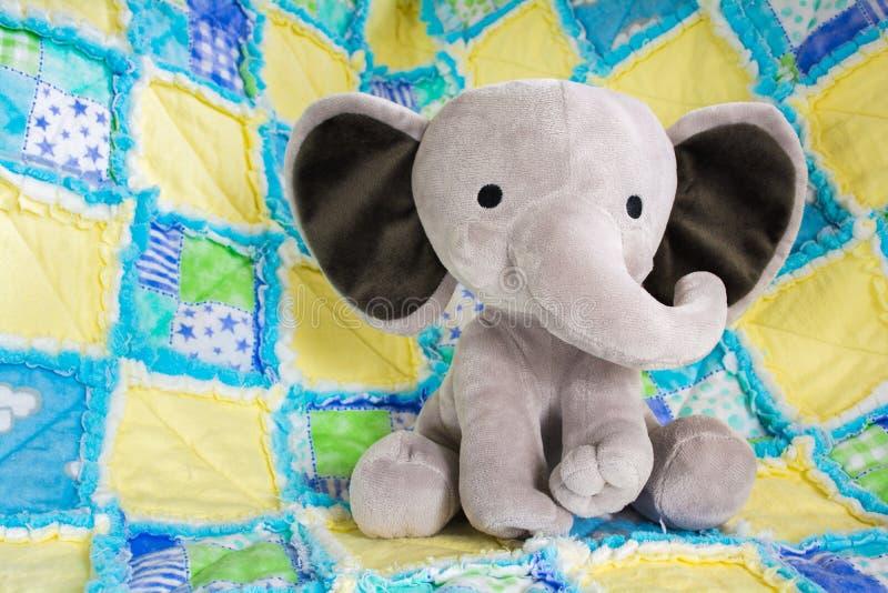 Nettes Baby-Elefant-Plüschtier auf buntem Steppdecken-Abschluss oben stockbild