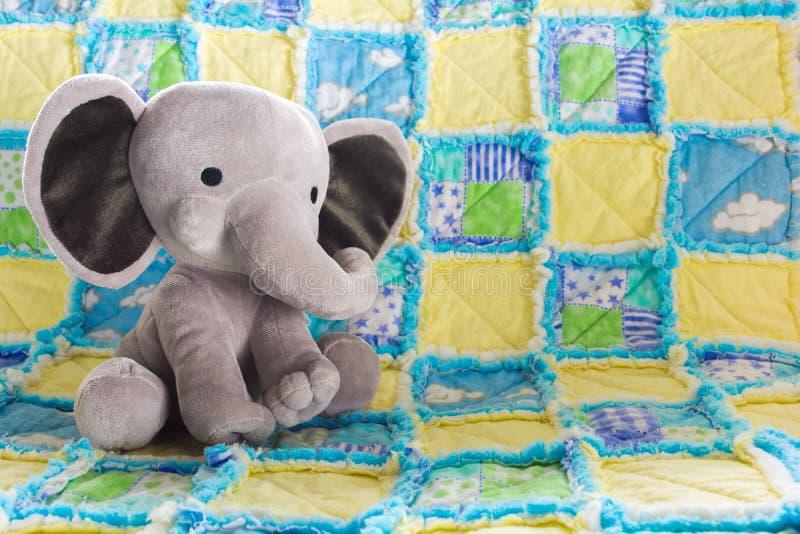 Nettes Baby-Elefant-Plüschtier auf einer bunten Steppdecke lizenzfreie stockfotos