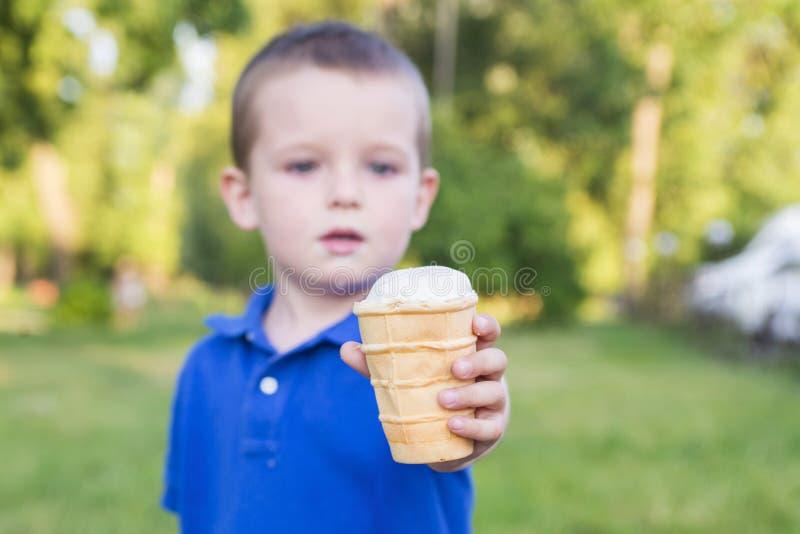 Nettes Baby, essen Eiscreme Ein Kind hält eine Eiscreme in seiner ausgestreckten Hand stockfotos