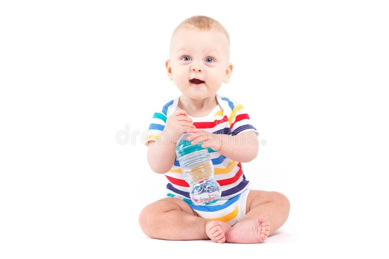 Nettes Baby im bunten Hemd mit Wasser stockfotos