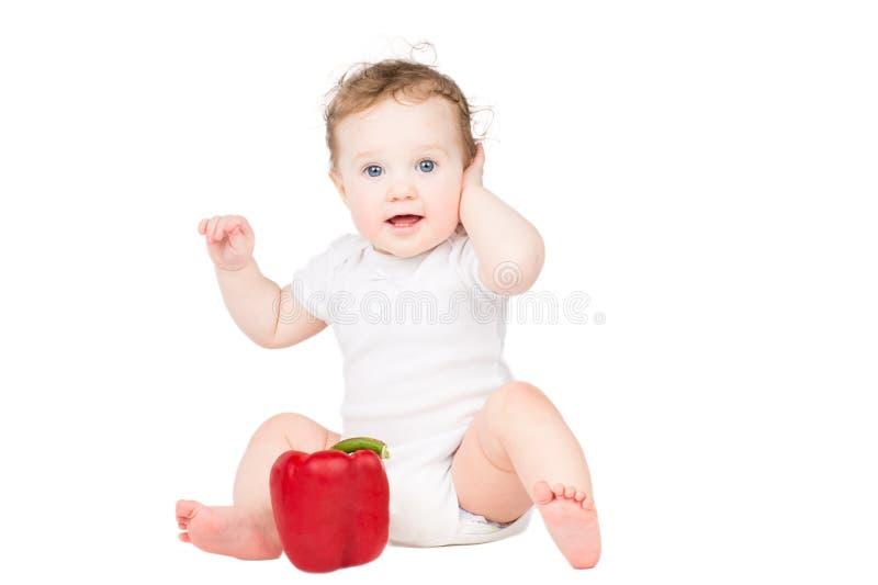 Nettes Baby mit dem gelockten Haar, das mit einem großen roten Paprika spielt lizenzfreie stockfotografie
