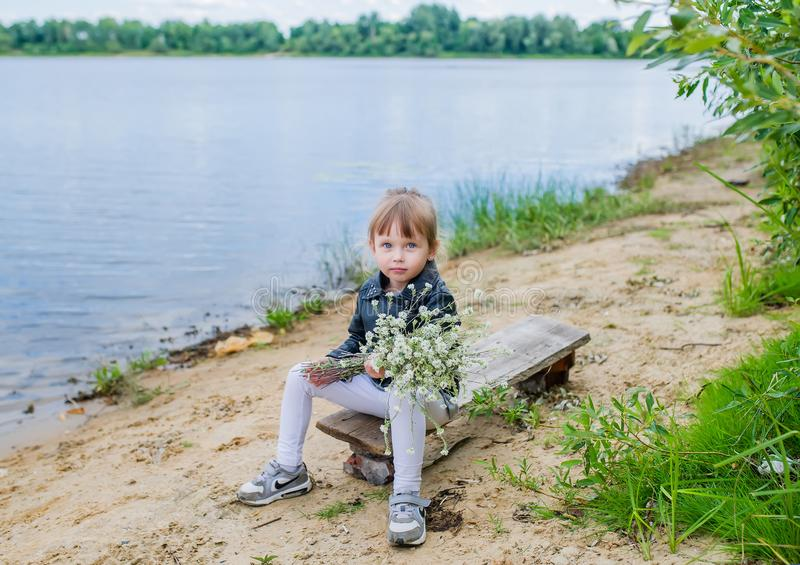 Nettes Baby mit einem Blumenstrauß von Wildflowers nahe See stockbilder