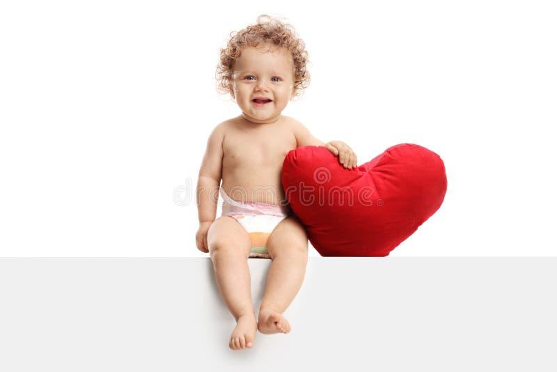 Nettes Baby mit einem Herzen formte das Kissen, das auf einer Platte sitzt lizenzfreies stockbild