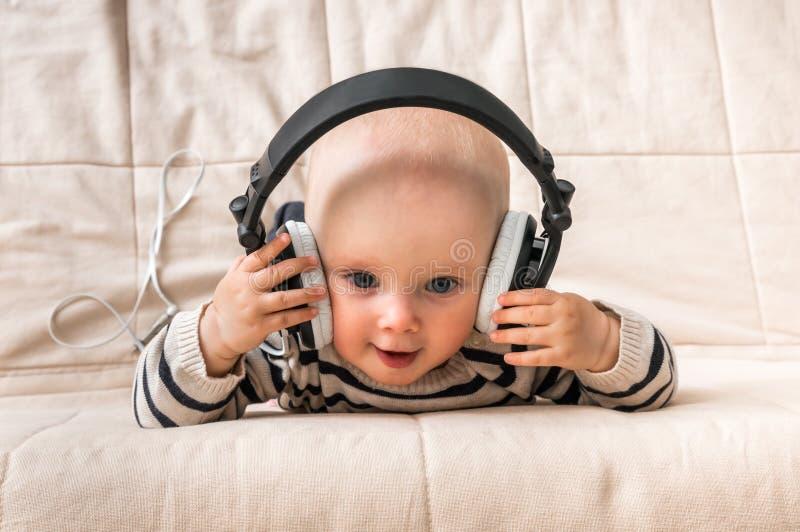 Nettes Baby mit Kopfhörern hört Musik zu Hause lizenzfreie stockbilder