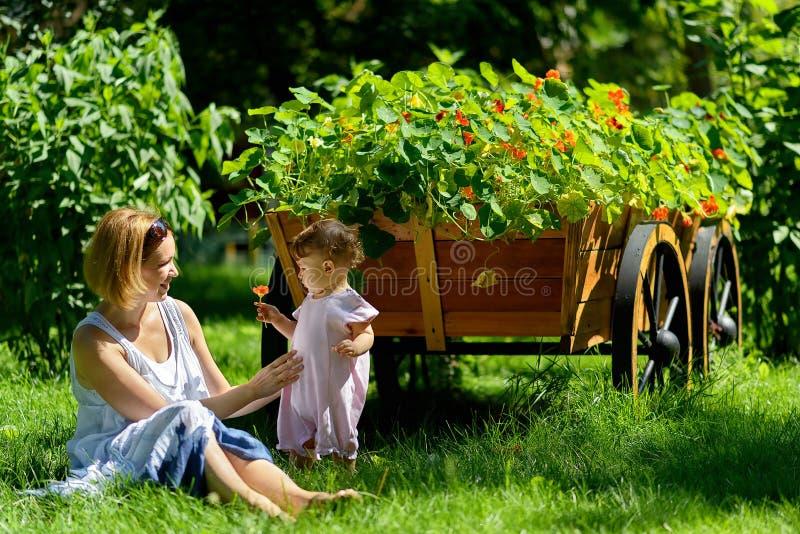 Nettes Baby mit Mutter in einem Garten mit Blume stockfotos