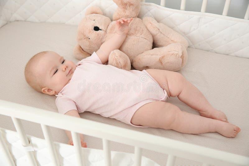 Nettes Baby mit Spielzeug in der Krippe stockfoto