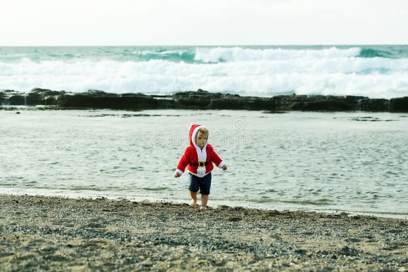 Nettes Baby in rotem Sankt-Mantel auf Pebble Beach lizenzfreies stockbild