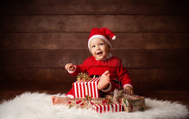 Nettes Baby Santa Claus Happy Smiling, die mit Weihnachtsgeschenken sitzt stockbilder