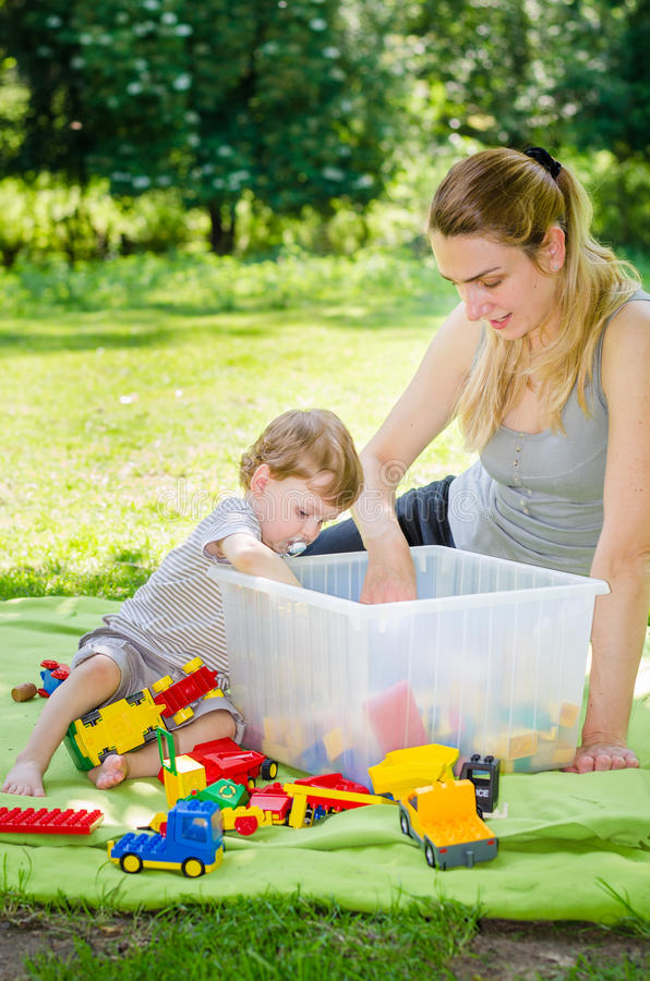 Nettes Baby spielt Spielwaren mit junger Mutter im Park stockfotos