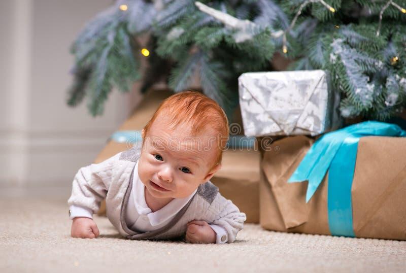 Nettes Baby unter Weihnachtsbaum stockbild