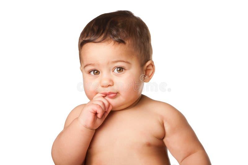 Nettes Babykind mit dem großen Finger der grünen Augen im Mund auf Weiß stockfotos