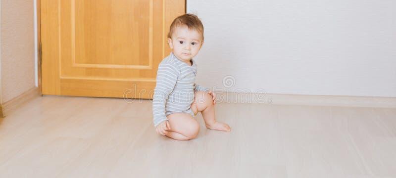Nettes Babykleinkind, das auf dem Boden im Schlafzimmer sitzt lizenzfreies stockbild