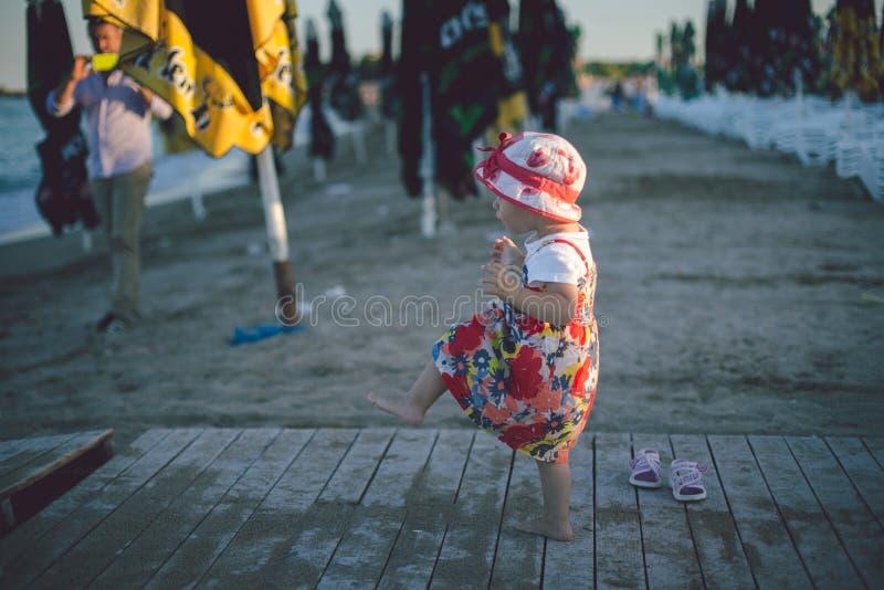 Nettes Babykleinkindmädchen auf dem Strand Sommer-Sonnenuntergang auf dem Strand lizenzfreie stockbilder