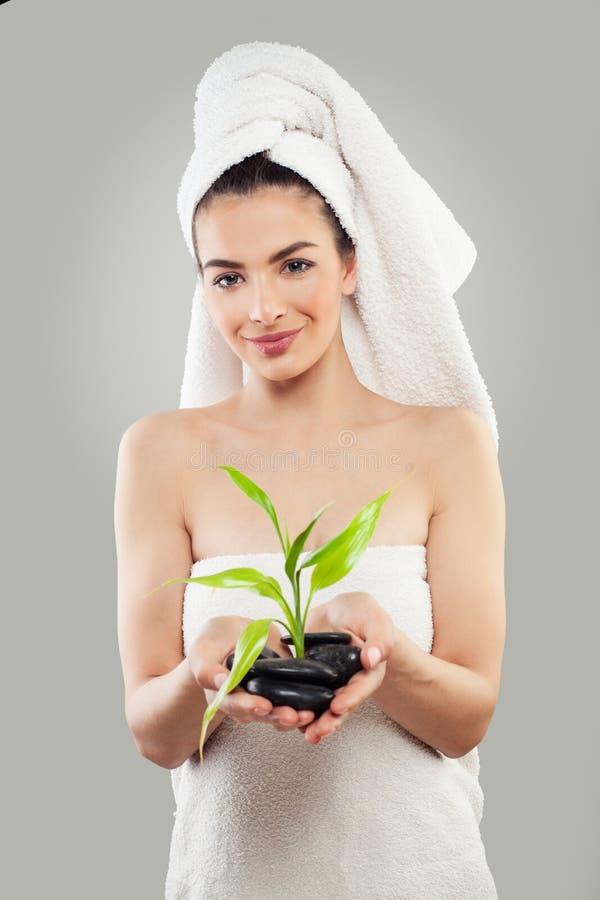 Nettes Badekurort-Mädchen mit grünen Bambus-Blättern und Massage-schwarzen Steinen stockfoto
