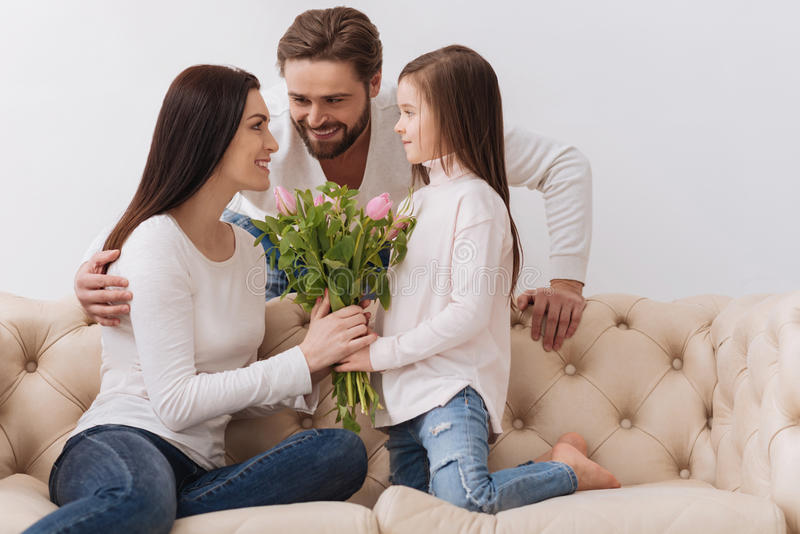 Nettes begeistertes Mädchen, das ihrer Mutter einen Blumenblumenstrauß gibt lizenzfreie stockfotos