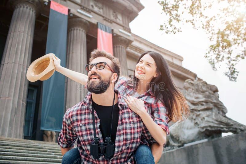 Nettes Bild der jungen Paarausgabenzeit zusammen Sie schauen in der gleichen Richtung Junger Mann hält Freundin auf Rückseite stockbild