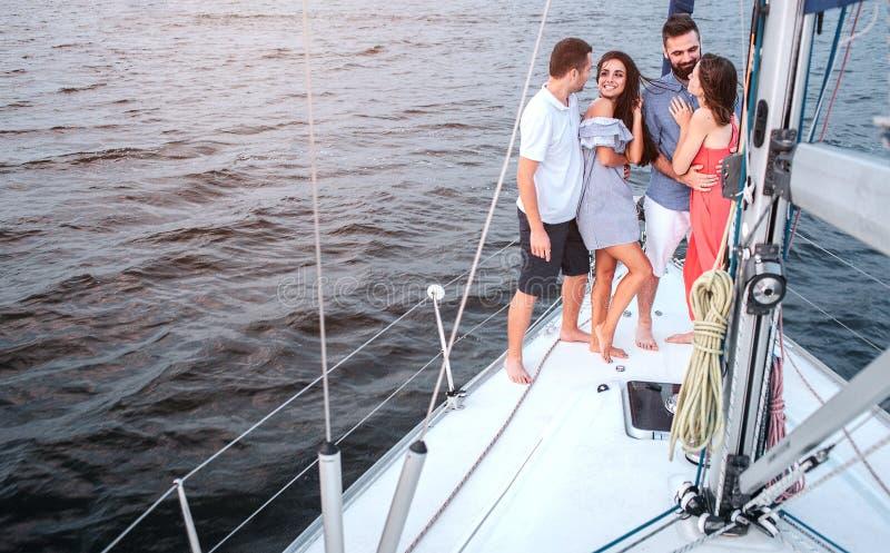 Nettes Bild von vier Leuten, die auf Yacht stehen Brunette betrachtet Kerl Sie lächelt Er umfasst sie Eine anderen Paare stockfotografie