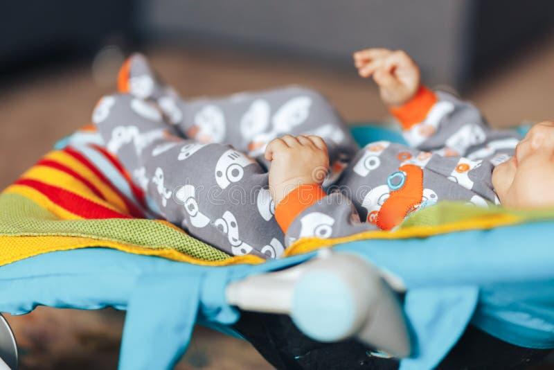 nettes blauäugiges Babykind, das auf sunbed oder einem farbigen Prahler des Klappstuhls zu Hause sich entspannt lizenzfreie stockbilder