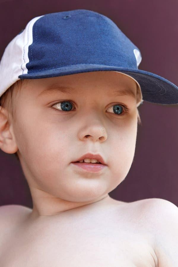 Nettes blondes Baby mit hellen blauen Augen in der blauen Kappe Gefühl des Spaßes, Freude, Aufmerksamkeit stockfoto