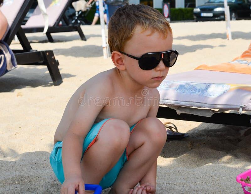 Nettes blondes ernstes Kind am Strand lizenzfreie stockfotografie