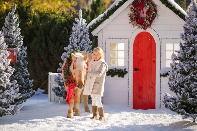 Nettes blondes gelocktes Mädchen und entzückendes Pony mit festlichem Kranz nahe dem kleinen Haus und den schneebedeckten Bäumen  stockfotos