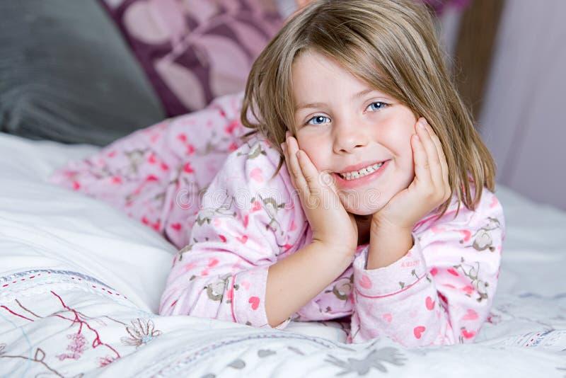 Nettes blondes Kind, das auf ihrem Bett liegt lizenzfreies stockfoto