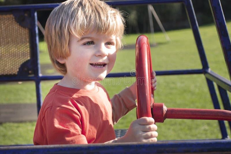 Nettes blondes Kind, das draußen in einem Spielplatz spielt stockbilder