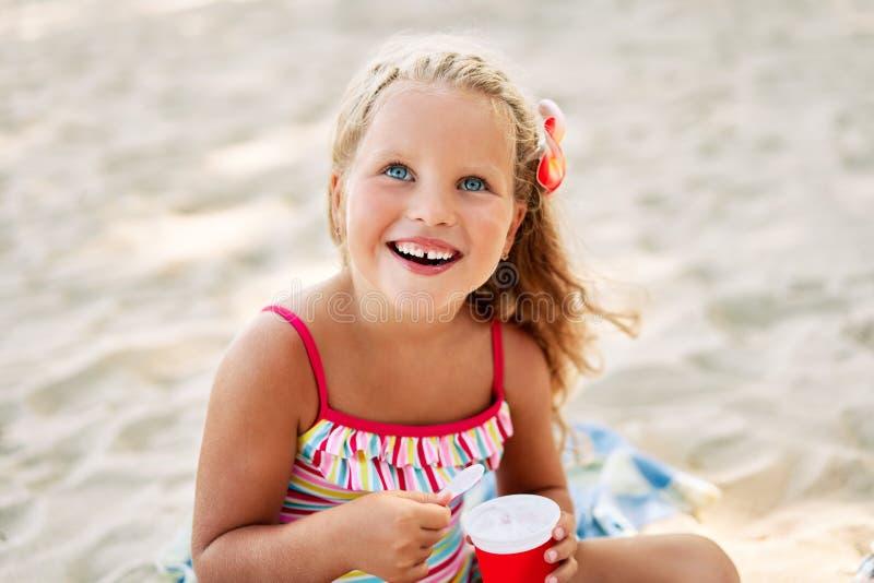 Nettes blondes kleines Mädchen, das Eiscreme auf sandigem Strand isst stockbilder