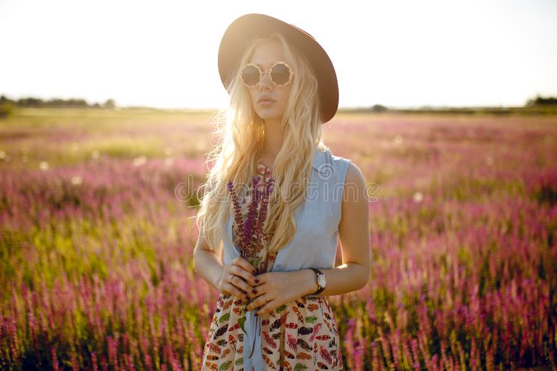 Nettes blondes Mädchen, das im Hut und in runder Sonnenbrille, gesetzt auf einem Blumengebiet, hinter schönem Sonnenunterganghint lizenzfreie stockfotografie