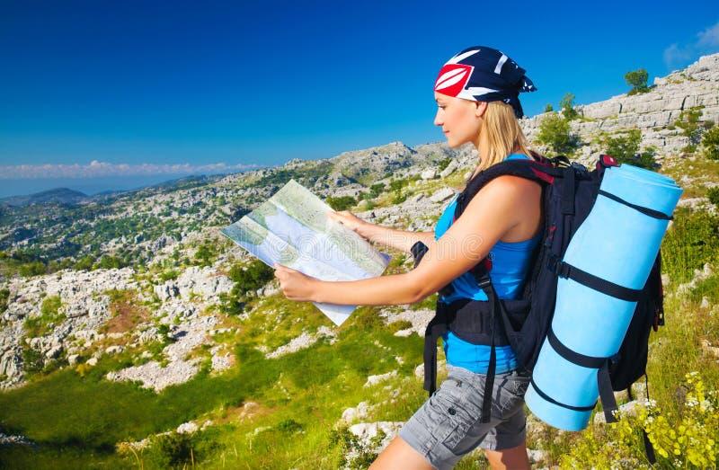 Nettes Mädchen in den Bergen, die zur Karte schauen lizenzfreie stockfotografie