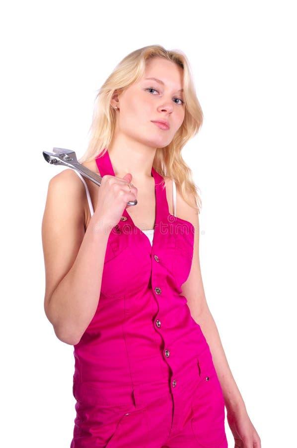 Nettes blondes Mädchen in den rosafarbenen Dungarees lizenzfreies stockfoto