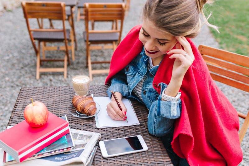 Nettes blondes Mädchen in der Denimjacke, die Einkaufsliste während der Mittagspause im Café im Freien macht Reizende junge Dame  lizenzfreies stockbild