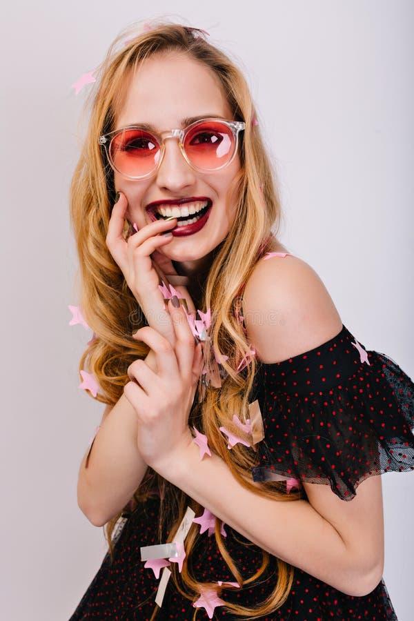 Nettes blondes Mädchen mit dem Finger im Mund, betrachtend glücklich und Kamera, photoshoot an der Partei nett Hat hübsches geloc stockfoto