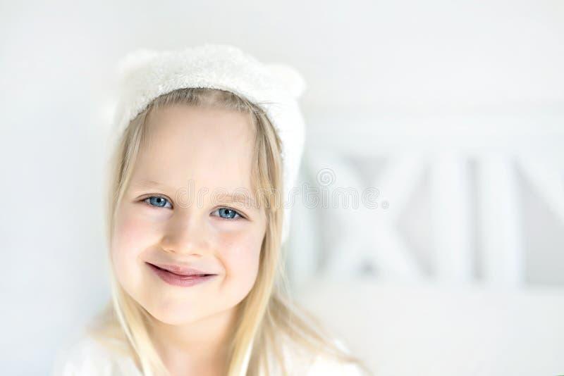 Nettes blondes Vorschülermädchen des Porträts Smillings-Kind im weißen Hut Kind auf Bett im Kindertagesstättenraum Entzückendes B lizenzfreie stockbilder
